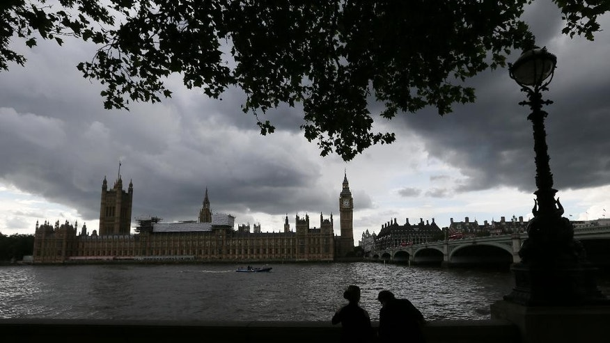 Under a lowering sky people view the Houses of Parliament from across the river Thames following yesterday's EU referendum result, London, Saturday, June 25, 2016.  Britain voted to leave the European Union after a bitterly divisive referendum campaign. (AP Photo/Tim Ireland)