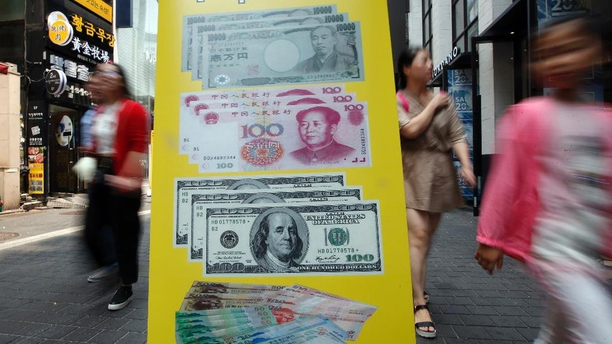Visitors walk by signs displaying foreign currency exchange rates at downtown Seoul, South Korea, Tuesday, June 28, 2016. South Korea's government lowered growth outlook for Asia's fourth-largest economy and planned a supplementary budget for a second year in a row as the global economy faces heightened uncertainty. (AP Photo/Lee Jin-man)