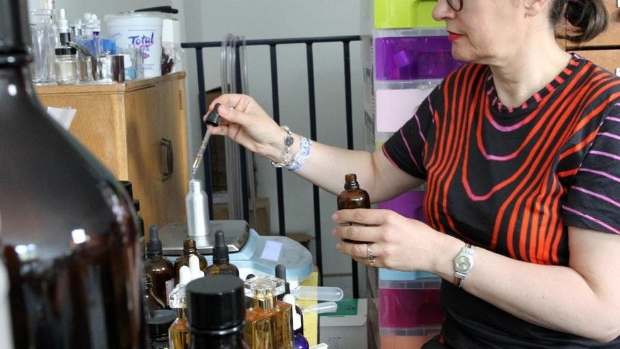 "Artisan perfume maker Sarah McCartney, 54, uses a dropper to put perfume into bottles at her business ""4160 Tuesdays"" in London, Monday, June 27, 2016. Faced with the prospect of years of uncertainty, businesses in Britain are already feeling the impact of last week's vote to leave the European Union. (AP Photo/Leonora Beck)"
