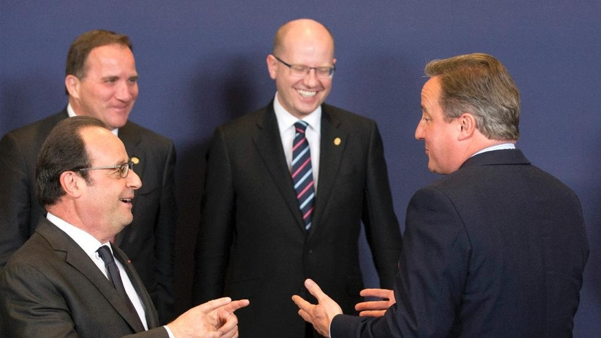 British Prime Minister David Cameron, right, speaks with French President Francois Hollande, left, during a group photo at an EU summit in Brussels on Tuesday, June 28, 2016. EU heads of state and government meet Tuesday and Wednesday in Brussels for the first time since Britain voted to leave the European Union, throwing British and European politics into disarray. (AP Photo/Geoffroy Van der Hasselt)