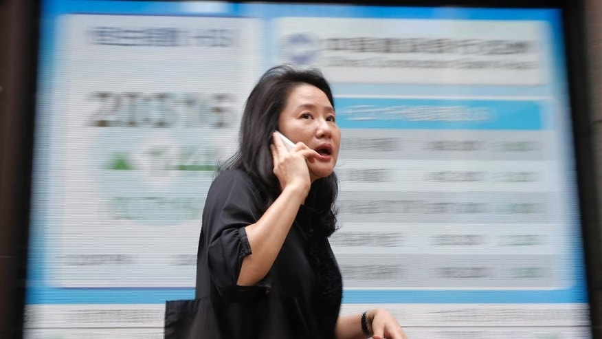 A woman walks passes a display of the Hang Seng Index at a bank in Hong Kong, Wednesday, June 29, 2016. Asian stock markets rallied on Wednesday following overnight gains on Wall Street and even bigger gains in Europe, as worries about uncertainty following Britain's EU referendum eased. (AP Photo/Kin Cheung)