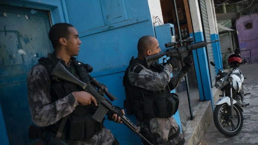 Officers take positions during a police operation against drug traffickers at the Jacarezinho slum in Rio de Janeiro, Brazil, Wednesday, June 29, 2016. Recent violence is adding to worries about safety in Rio during the Olympics. Officials have warned that budget shortfalls may compromise security during the games. (AP Photo/Felipe Dana)