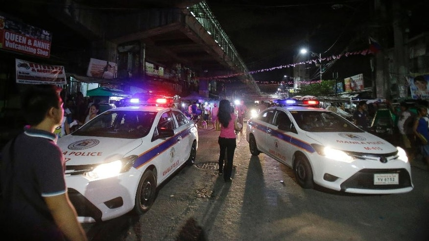 In this June 8, 2016 file photo, police cars block a street as they enforce an overnight curfew for minors in Manila, Philippines. Even before he takes his oath of office on Thursday, Philippine President-elect Rodrigo Duterte's vow to kill drug criminals appear already being rolled out. At least dozens of suspected drug criminals have either been killed in shootouts with police or mysteriously found dead on the streets in what some fear is a portent of things to come. (AP Photo/Aaron Favila)