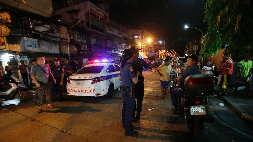 In this June 8, 2016 file photo, police conduct an overnight curfew for minors in Manila, Philippines. Even before he takes his oath of office on Thursday, Philippine President-elect Rodrigo Duterte's vow to kill drug criminals appear already being rolled out. Dozens of suspected drug criminals have either been killed in shootouts with police or mysteriously found dead on the streets in what some fear is a portent of things to come. (AP Photo/Aaron Favila)