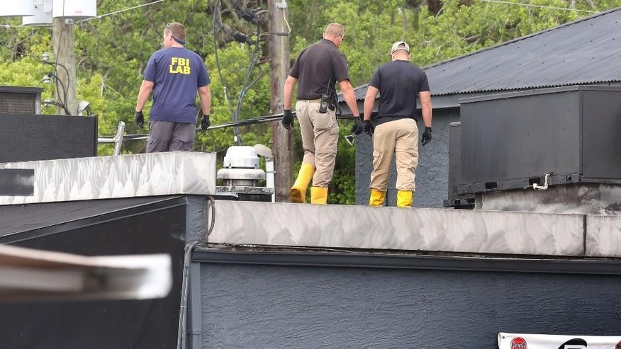FBI lab personnel walk on the roof of the Pulse Nightclub June 20.