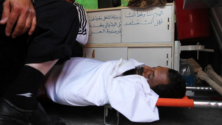 In this Sunday, June 19, 2016 photo, a man outside the al-Maktoum mosque in Zarqa, Jordan squats over the body of Nasser Idreis, who died of complications of a liver infection while serving a three-year prison term for supporting the extremist group Islamic State. Hundreds of suspected backers of the Islamic State group in Jordan have been sentenced to prison, are awaiting trial or are being held for questioning in a heavy crackdown by the kingdom under toughened anti-terror laws that punish even liking or sharing IS material on social media. (Layla Quran/AP Photo)