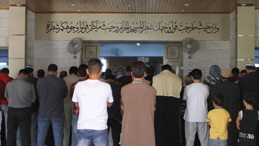 In this Sunday, June 19, 2016 photo, men pray inside the al-Makhtoum mosque in Zarqa, Jordan during the funeral of Nasser Idreis, an alleged Islamic State sympathizer who died serving a three-year prison sentence. Hundreds of suspected backers of the Islamic State group in Jordan have been sentenced to prison, are awaiting trial or are being held for questioning in a heavy crackdown by the kingdom under toughened anti-terror laws that punish even liking or sharing IS material on social media. (Layla Quran/AP Photo)