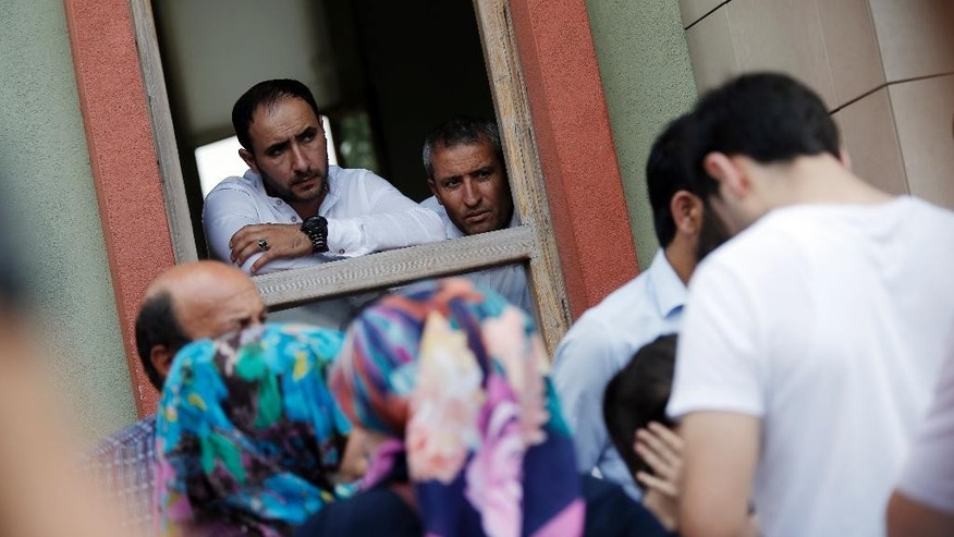Forensic officials look at family members of victims who are crying outside the Forensic Medical Center in Istanbul, Wednesday, June 29, 2016. Suicide attackers killed dozens and wounded more than 140 at Istanbul's busy Ataturk Airport late Tuesday, the latest in a series of bombings to strike Turkey in recent months. Turkish officials said the massacre was most likely the work of the Islamic State group. Turkish authorities have banned distribution of images relating to the Ataturk airport attack within Turkey.(AP Photo/Emrah Gurel) TURKEY OUT