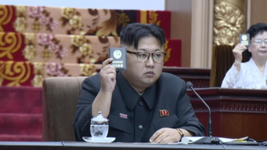 North Korean leader Kim Jong Un raises his Party Membership Card to vote during North Korea's Supreme People's Assembly,  convened Wednesday June 29, 2016, in Pyongyang, North Korea.  Kim Jong Un vowed to continue developing nuclear weapons while also strengthening the country's economy. (NKO via AP Photo)