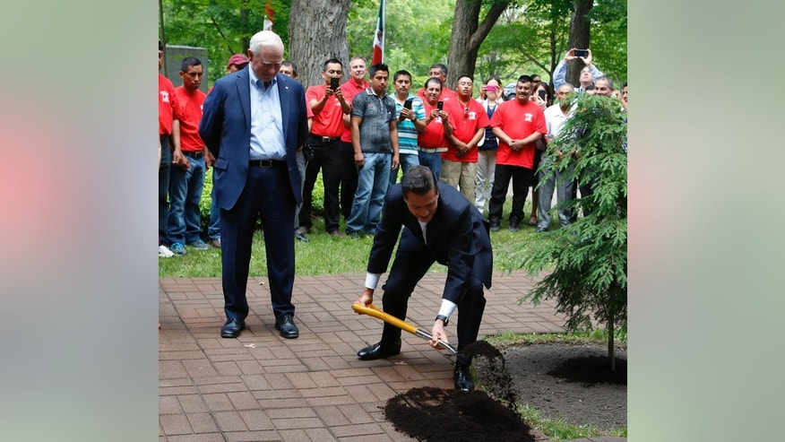 Mexican President Enrique Pena Nieto, right, takes part in a tree planting ceremony as Governor General David Johnston looks on at the grounds of Rideau Hall, the official residence of the Governor General, to commemorate Nieto's visit to Ottawa, Tuesday, June 28, 2016. (Fred Chartrand/The Canadian Press via AP) MANDATORY CREDIT
