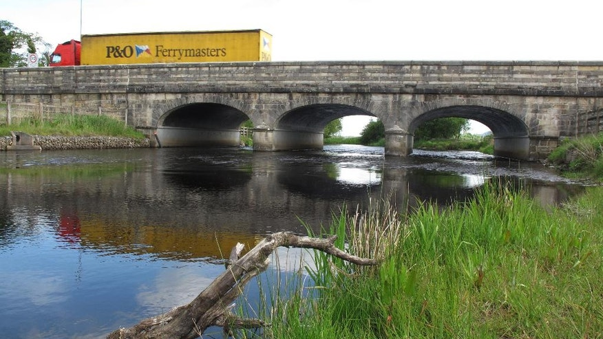 FILE - This is Wednesday, May 25, 2016 file photo of a  truck as it crosses the bridge from Blacklion, Republic of Ireland, into Belcoo, Northern Ireland, . The bridge has no signs indicating the presence of an international border besides the posted speed limits which are listed in British miles going north into Northern Ireland, and in kilometers going south into the Republic of Ireland.  All along the meandering 310-mile (500-kilometer) Northern Ireland border with the Irish Republic, residents are trying to imagine what life will be like if Northern Ireland, like the rest of the U.K., actually leaves the 28-nation EU. (AP Photo/Shawn Pogatchnik)