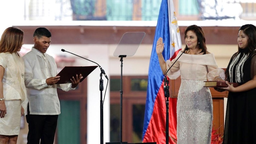 "Philippine Vice President Leni Robredo, second right, is sworn in by village chiefs Ronaldo Coner and Regina Celeste during inauguration ceremonies in suburban Quezon city, north of Manila, Philippines Thursday June 30, 2016. Robredo won over Sen. Ferdinand ""Bongbong"" Marcos Jr., the son of the late strongman Ferdinand Marcos, in a closely-contested race on May 9 which also resulted in the presidential victory of Rodrigo Duterte, who will be separately sworn in Thursday at the Malacanang presidential palace. (AP Photo/Aaron Favila)"