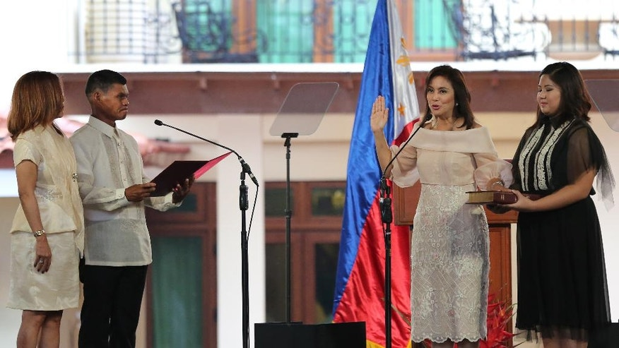 """Philippine Vice President Leni Robredo, second right, is sworn in by village chiefs Ronaldo Coner and Regina Celeste during inauguration ceremonies in suburban Quezon city, north of Manila, Philippines Thursday June 30, 2016. Robredo won over Sen. Ferdinand """"Bongbong"""" Marcos Jr., the son of the late strongman Ferdinand Marcos, in a closely-contested race on May 9 which also resulted in the presidential victory of Rodrigo Duterte, who will be separately sworn in Thursday at the Malacanang presidential palace. (AP Photo/Aaron Favila)"""