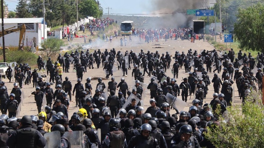 In this Sunday, June 19, 2016 photo, riot police are forced to fall back as they battle with protesting teachers who were blocking a federal highway in the state of Oaxaca, near the town of Nochixtlan, Mexico. The teachers are protesting against plans to overhaul the country's education system which include federally mandated teacher evaluations. (AP Photo/Luis Alberto Cruz Hernandez)