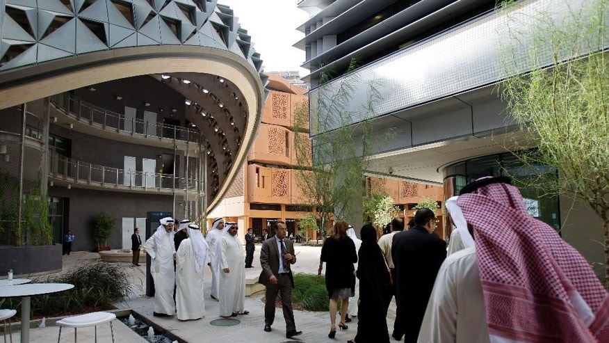 FILE - In this Sunday, Jan. 16, 2011 file photo, People visit the Masdar Institute campus, part of Masdar City, a Mubadala company, in Abu Dhabi, United Arab Emirates. A top official in the United Arab Emirates has issued an order for the merging of two of the Gulf nation's most prominent government wealth funds, streamlining the country's investment strategy as it weathers a slump in oil prices. (AP Photo/Kamran Jebreili, File)