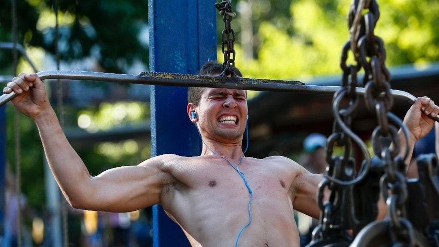 In this photo taken Saturday, June 25, 2016 a man trains in the outdoor gym on an island on the Dnieper River in Kiev, Ukraine. Every day hundreds of people flock to Kiev's legendary gym on the Dnieper island which dates back to the 1960s. (AP Photo/Sergei Chuzavkov)
