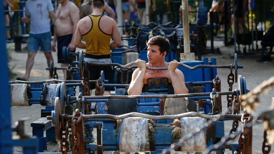 In this photo taken Thursday, June 23, 2016, a man trains in the outdoor gym on an island on the Dnieper River in Kiev, Ukraine. Every day hundreds of people flock to Kiev's legendary gym on the Dnieper island which dates back to the 1960s. (AP Photo/Sergei Chuzavkov)