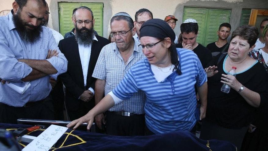 Rina Ariel touches the body of her slain 13 year old daughter Hallel during her funeral inside a Jewish settlement of Kiryat Arba, West Bank, Thursday, June 30, 2016. A Palestinian youth sneaked into a fortified Jewish settlement in the West Bank on Thursday, broke into a home and fatally stabbed Hallel, Israeli-American girl, as she slept in bed before security guards arrived and killed him.(AP Photo/Olivier Fitoussi) ***ISRAEL OUT***
