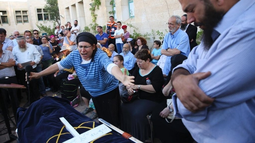 Rina Ariel weeps over the body of her slain 13 year old daughter Hallel during her funeral inside a Jewish settlement of Kiryat Arba, West Bank, Thursday, June 30, 2016. A Palestinian youth sneaked into a fortified Jewish settlement in the West Bank on Thursday, broke into a home and fatally stabbed Hallel, Israeli-American girl, as she slept in bed before security guards arrived and killed him.(AP Photo/Olivier Fitoussi) ***ISRAEL OUT***