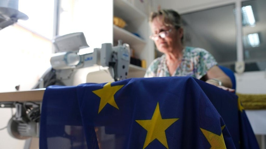 A seamstress sews an EU flag in a workshop in Belgrade, Serbia, Wednesday, June 29, 2016. Serbia, Montenegro, Macedonia, Bosnia, Kosovo and Albania, all at different stages in joining the EU, have declared that the British exit in a referendum last week will not diminish their membership efforts. (AP Photo/Darko Vojinovic)