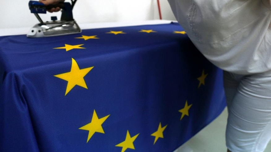 A seamstress irons an EU flag in a workshop in Belgrade, Serbia, Wednesday, June 29, 2016. Serbia, Montenegro, Macedonia, Bosnia, Kosovo and Albania, all at different stages in joining the EU, have declared that the British exit in a referendum last week will not diminish their membership efforts. (AP Photo/Darko Vojinovic)