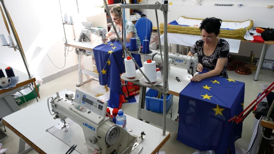 Seamstresses sews EU flags in a workshop in Belgrade, Serbia, Wednesday, June 29, 2016. Serbia, Montenegro, Macedonia, Bosnia, Kosovo and Albania, all at different stages in joining the EU, have declared that the British exit in a referendum last week will not diminish their membership efforts. (AP Photo/Darko Vojinovic)