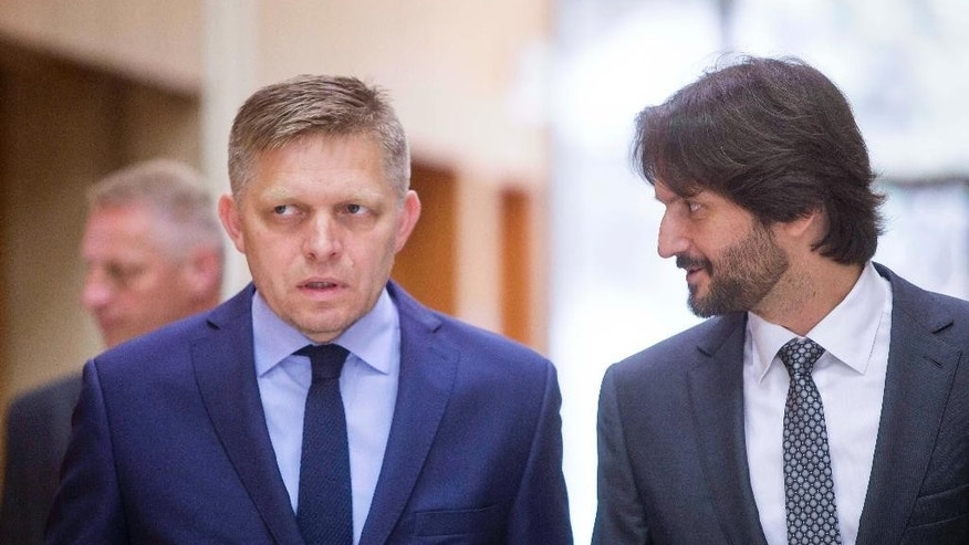 Slovakia's Prime Minister Robert Fico, left, talks to Ministry of the Interior Robert Kalinak, right, prior a government meeting in Bratislava, Slovakia, Thursday, June 30, 2016.  Slovakia will undertake their six-month presidency of the European Union from July  2016. (AP Photo/Bundas Engler)