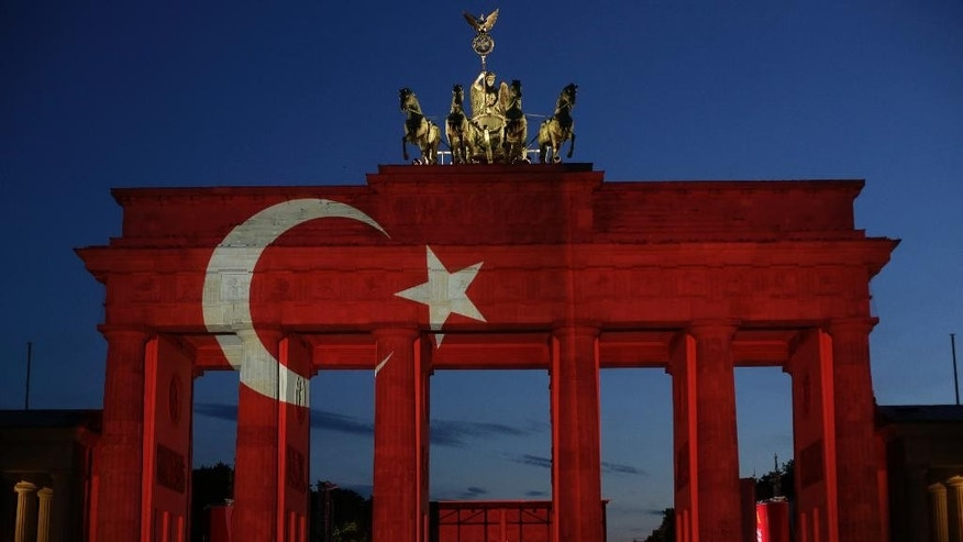 The Turkey flag is illuminated onto the Brandenburg Gate in Berlin, Wednesday, June 29, 2016. The Brandenburg Gate was illuminated with Turkey's national flag after suicide attackers killed dozens and wounded more than 140 at Istanbul's busy Ataturk Airport late Tuesday, the latest in a series of bombings to strike Turkey in recent months. (AP Photo/Markus Schreiber)