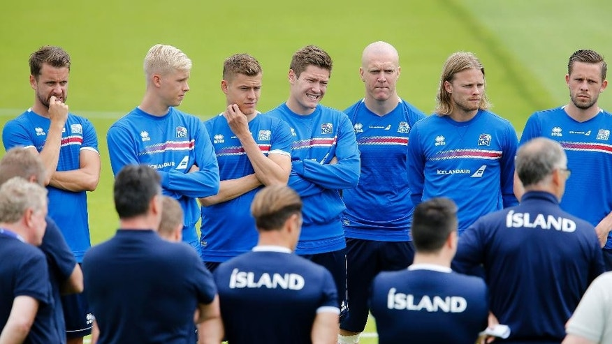 Players listen to the coach as they attend a training session of Iceland's national soccer team at their base camp in Annecy, France, Thursday, June 30, 2016. Iceland will face France in a Euro 2016 quarterfinal match in Paris on Sunday, July 3, 2016.(AP Photo/Michael Probst)