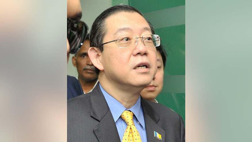FILE - In this June 29, 2016, file photo, Lim Guan Eng, chief minister of northern Penang state, is arrested by the Malaysian Anti-Corruption Commission (MACC) at his office in Penang island, Malaysia. Lim, a Malaysian opposition politician who has strongly criticized financial scandals involving Prime Minister Najib Razak, has been charged with corruption on Thursday, June 30, 2016. (AP Photo/Gary Chuah, File)