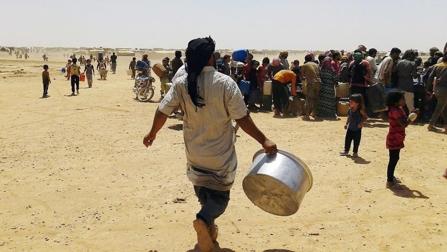 In this Tuesday, June 28, 2016 photo, Syrian refugees gather for water at Ruqban border camp in northeast Jordan. Syrian refugees and international aid officials say little water and no food has reached 64,000 Syrian refugees stranded in the desert since Jordan sealed its border in response to a suicide attack on June 21, 2016. (AP Photo)