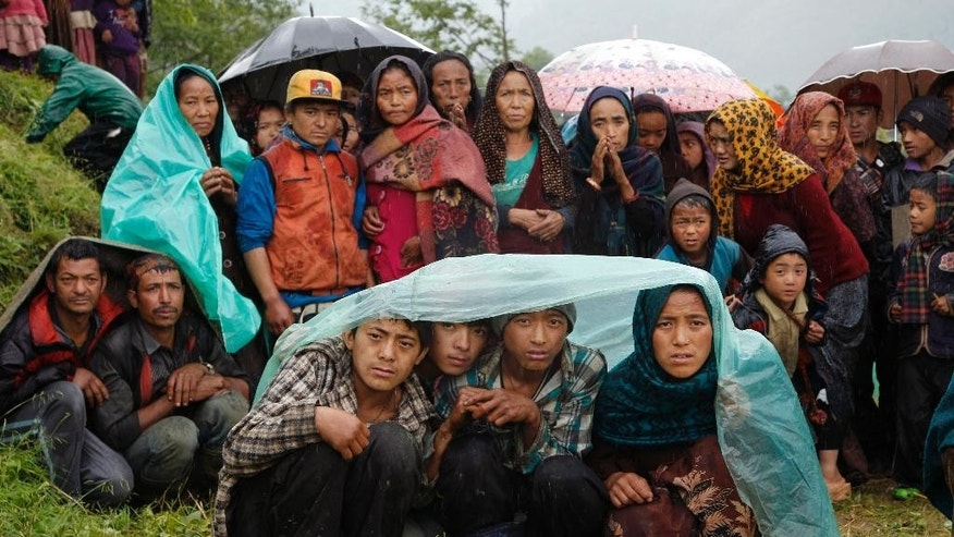 FILE - In this April 29, 2015, file photo, villagers wait in the rain as an aid relief helicopter lands at their remote mountain village of Gumda, near the epicenter of the April 25 massive earthquake in the Gorkha District of Nepal. Nepal's government agreed Thursday, June 30, 2016, to speed up aid grants to quake victims by providing the grants in two installments instead of three as was planned earlier. (AP Photo/Wally Santana, File)