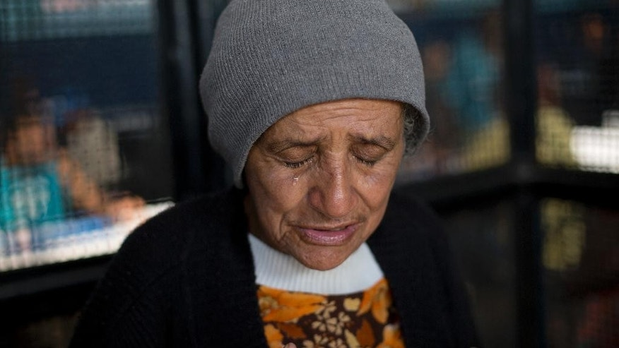 An elderly woman cries after finding out that Central do Brasil soup kitchen will be closed, in Rio de Janeiro, Brazil, Thursday, June 30, 2016. Some of Rio de Janeiro's busy soup kitchens are shutting down because the cash-strapped state has failed to pay suppliers that serve cheap meals to the poor. It's the latest fallout from a financial crisis that is also fueling worries about security and public transportation during the summer olympic games slated to begin Aug. 5.(AP Photo/Silvia Izquierdo)