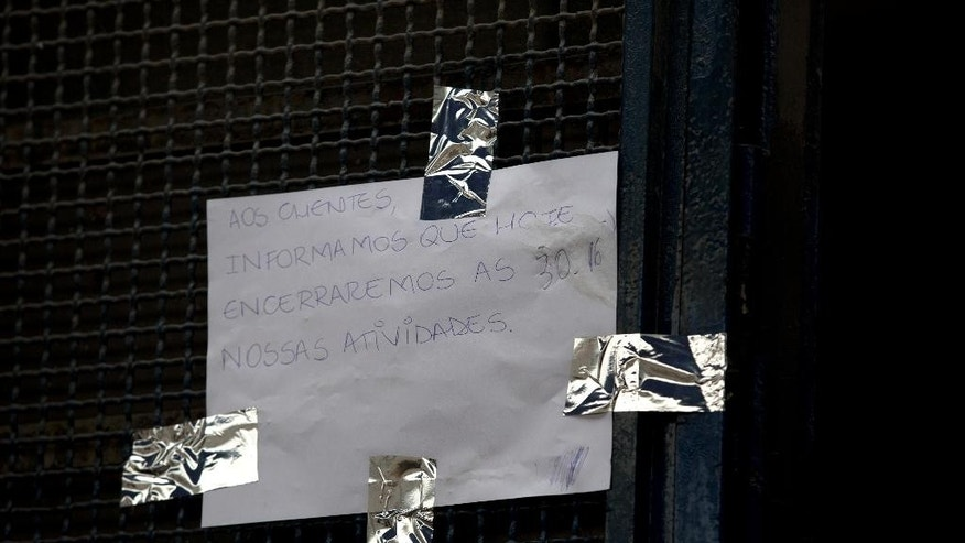 "A sign that reads in Portuguese ""To the clients, we inform that today we will closed our activities on 30/16"" hangs at the door of the Central do Brasil soup kitchen in Rio de Janeiro, Brazil, Thursday, June 30, 2016. Some of Rio de Janeiro's busy soup kitchens are shutting down because the cash-strapped state has failed to pay suppliers that serve cheap meals to the poor. It's the latest fallout from a financial crisis that is also fueling worries about security and public transportation during the summer olympic games slated to begin Aug. 5. (AP Photo/Silvia Izquierdo)"