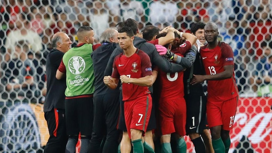 Portugal's Cristiano Ronaldo foreground celebrates past teammates at the end of the Euro 2016 quarterfinal soccer match between Poland and Portugal, at the Velodrome stadium in Marseille, France, Thursday, June 30, 2016. Portugal won 5-3 in a penalty shootout. (AP Photo/Frank Augstein)
