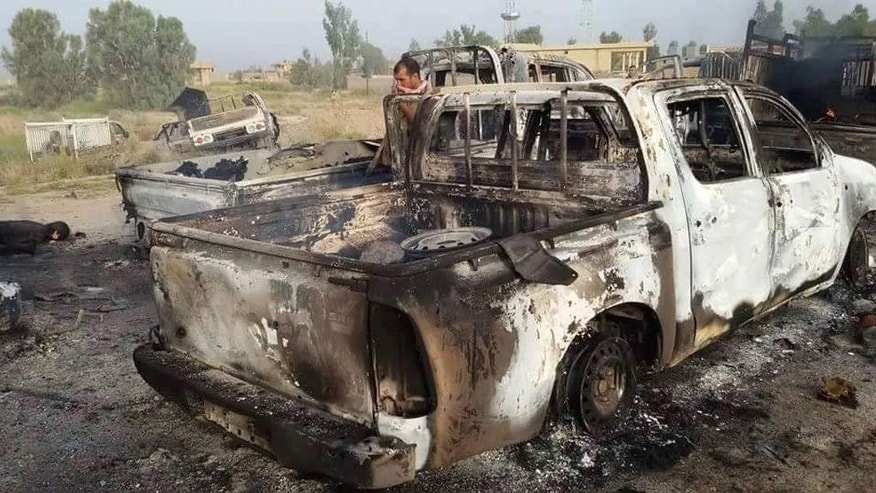 This image released by Iraq's Counterterrorism Service shows a destroyed militant vehicle after Coalition and Iraqi security forces targeted Islamic State fighters fleeing the outskirts of Fallujah, Iraq on Wednesday, June 29, 2016. Iraq's Defense Ministry has released footage showing airstrikes on dozens of vehicles, which officials said was an IS convoy fleeing the western city of Fallujah following its recapture by the Iraqi military.(Iraq Counterterrorism Service via AP)