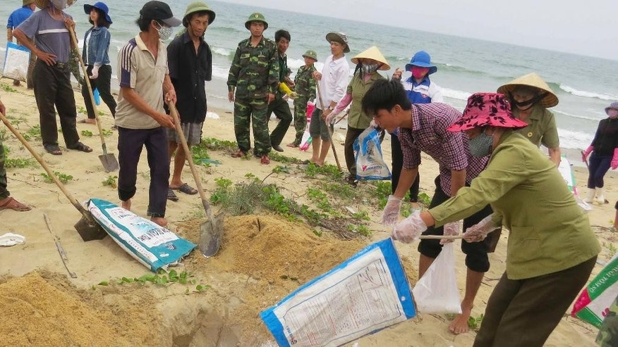 In this April 28, 2016, photo, villagers bury dead fish on a beach in Quang Binh, Vietnam. Vietnam's government announced Thursday, June 30, 2016, that Taiwan's Formosa Ha Tinh Steel Corp. was responsible for an estimated 70 tons of dead fish that began washing ashore along more than 200 kilometers (125 miles) of coastline in four central provinces in early April. The company has pledged to pay $500 million in compensation.(Vo Thi Dung/VNA via AP)
