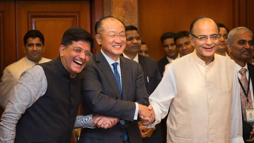 World Bank President Jim Yong Kim, center, shakes hand with Indian Finance Minister Arun Jaitley, right, and Indian Power and Renewable Energy Minister Piyush Goyal after signing a deal to boost solar energy globally, in New Delhi, India, Thursday, June 30, 2016. The World Bank Group Thursday signed an agreement with the International Solar Alliance, consisting of 121 countries led by India, to collaborate on increasing solar energy use around the world, with the goal of mobilizing $1 trillion in investment by 2030. (AP Photo/Manish Swarup)