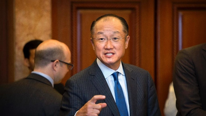 World Bank President Jim Yong Kim, center, talks to his colleague after signing a deal to boost solar energy globally, in New Delhi, India, Thursday, June 30, 2016. The World Bank Group Thursday signed an agreement with the International Solar Alliance, consisting of 121 countries led by India, to collaborate on increasing solar energy use around the world, with the goal of mobilizing $1 trillion in investment by 2030. (AP Photo/Manish Swarup)