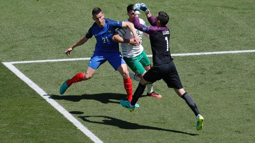 France goalkeeper Hugo Lloris, right, clears a ball followed by Ireland's Shane Long, center and France's Laurent Koscielny during the Euro 2016 round of 16 soccer match between France and Ireland, at the Grand Stade in Decines-Charpieu, near Lyon, France, Sunday, June 26, 2016. (AP Photo/Michael Sohn)