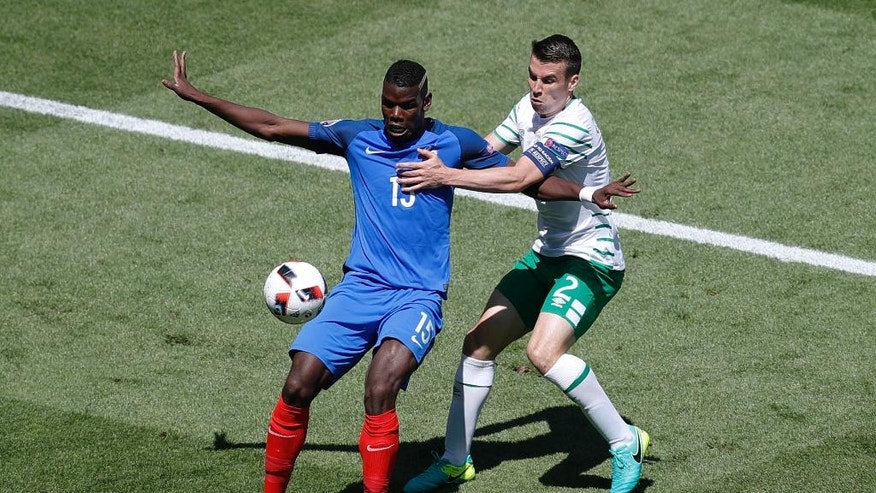 France's Paul Pogba, left, challenges for the ball with Ireland's Seamus Coleman, right, during the Euro 2016 round of 16 soccer match between France and Ireland, at the Grand Stade in Decines-Charpieu, near Lyon, France, Sunday, June 26, 2016. (AP Photo/Michael Sohn)