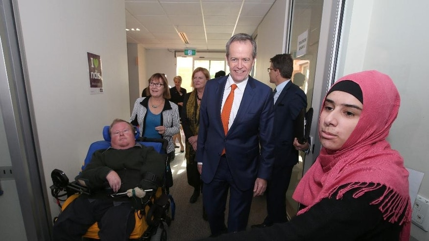 Australia's opposition Labor Party leader Bill Shorten, center, is taken on a tour of a disability center in Sydney, Friday, July 1, 2016. Shorten is campaigning on the last day before a national election. (AP Photo/Rick Rycroft)