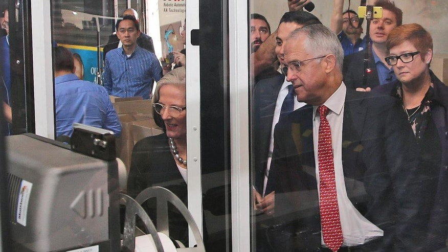 Australia's Prime Minister Malcolm Turnbull watches a robotic packing machine during his visit to a small business factory in the western suburbs of Sydney, Australia, Friday, July 1, 2016. Australians go to the polls Saturday with the opposition leader vying to become the country's fifth prime minister in three years. (AP Photo/Rob Griffith)
