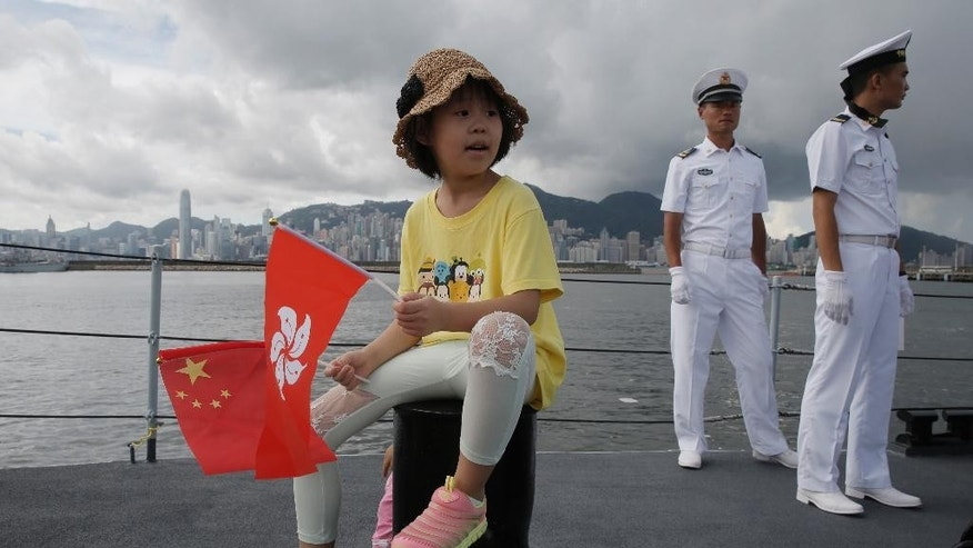 A girl holds China and Hong Kong national flags during the open day of Chinese People's Liberation Army (PLA) Navy Base at Stonecutter Island, in Hong Kong to mark the 19th anniversary of the Hong Kong handover to China, Friday, July 1, 2016. (AP Photo/Kin Cheung)