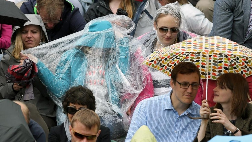 Spectators take shelter from the rain during day five of the Wimbledon Tennis Championships in London, Friday, July 1, 2016. (AP Photo/Tim Ireland)