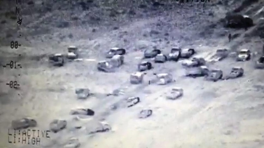 This image made from video released by Iraq's Counterterrorism Service shows an Islamic State militant convoy destroyed by airstrikes near Fallujah, Iraq on Wednesday, June 29, 2016. They fled swiftly and in droves, convoys of the last remaining Islamic State fighters abandoning Fallujah, the Iraqi city they had held for more than two years, melting into the sprawling Anbar desert. Behind them, they left clumps of hair from beards hastily shaven so they could later easier blend into the civilian population. The victorious Iraqi army says it bombed convoys of fleeing jihadis, destroying dozens of vehicles. But they way IS quickly abandoned a long-held stronghold underscores its ability to adapt and regroup, long after defeat on the battlefield.  (Iraq Counterterrorism Service via AP)
