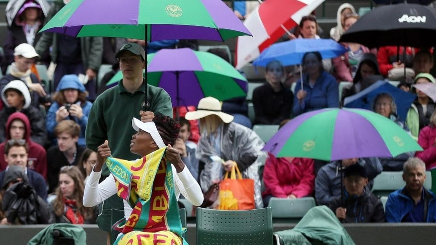 Venus Williams of the U.S looks out as rain delays her women's singles match against Daria Kasatkina of Russia on day five of the Wimbledon Tennis Championships in London, Friday, July 1, 2016. (AP Photo/Tim Ireland)