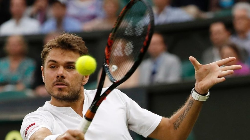Stan Wawrinka of Switzerland returns to Juan Martin del Potro of Argentina during their men's singles match on day five of the Wimbledon Tennis Championships in London, Friday, July 1, 2016. (AP Photo/Ben Curtis)