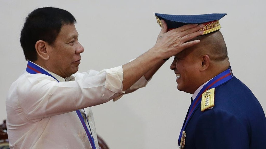 "Philippine President Rodrigo Duterte, left, places the hat of the new Police Chief, Director General Ronald Dela Rosa, during the ""Assumption of Command"" ceremonies at Camp Crame, Philippine National Police headquarters, in suburban Quezon city, Manila, Philippines, on Friday, July 1, 2016. Duterte, who was sworn in as the Philippines' 16th president, has given himself a colossal campaign promise to fulfill, eradicating crime especially drug trafficking, smuggling, rapes and murder in three to six months. (AP Photo/Aaron Favila)"