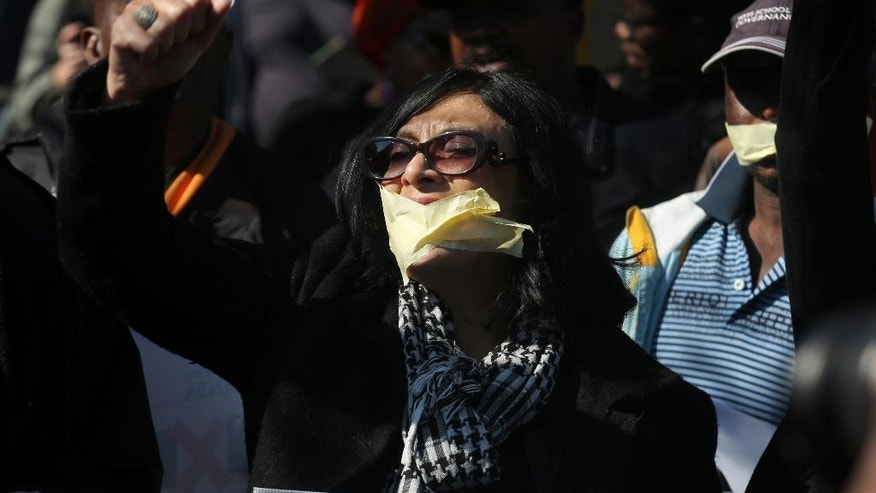 Protesters with mouths taped shut in Johannesburg, Friday July 1, 2016, as journalists and members of the public demonstrate outside the South African Broadcasting Corporation (SABC) headquarters in solidarity with three SABC journalists who were suspended for expressing their concerns about editorial policy amid allegations of newsroom censorship. (AP Photo/Denis Farrell) .